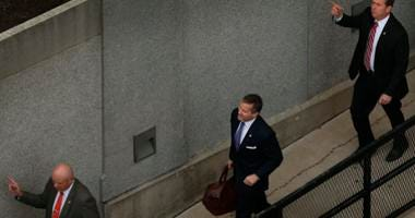 Flanked by security guards, Missouri Gov. Eric Greitens, center, arrives at court for jury selection in his felony invasion of privacy trial, Thursday, May 10, 2018, in St. Louis.