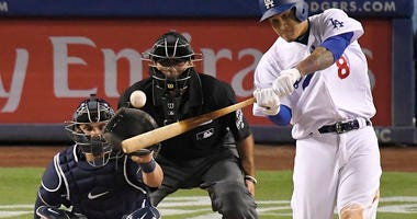 Los Angeles Dodgers' Manny Machado, right, hits a solo home run a