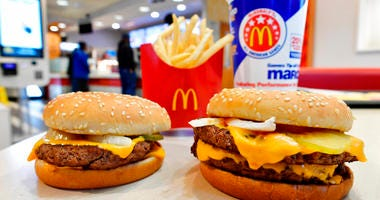 FILE- In this March 6, 2018, file photo, a McDonald's Quarter Pounder, left, and Double Quarter Pound burger is shown with fresh beef in Atlanta.