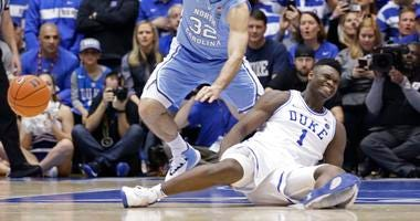 Duke's Zion Williamson sits on the floor following a injury during the first half of an NCAA college basketball game against North Carolina, in Durham, N.C., Wednesday, Feb. 20, 2019.