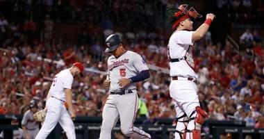 Minnesota Twins' Eduardo Escobar (5) scores between St. Louis Cardinals starting pitcher John Gant, left, and catcher Carson Kelly.