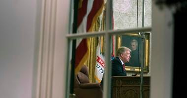 President Donald Trump is seen through the window of the Oval Office as he delivers a primetime address on the government shutdown