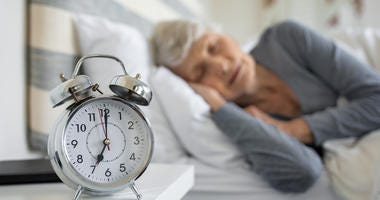 lady sleeping with alarm clock in front