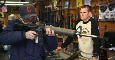 man looking through rifle before purchasing gun