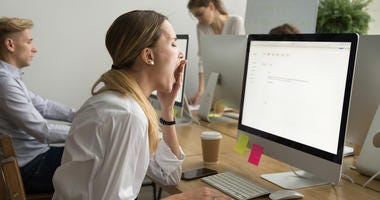 woman yawning at computer desk