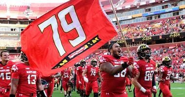 Maryland Terrapins offensive lineman Ellis McKennie (68) runs onto the field with his teammates holding a flag in remembrance of Jordan McNair