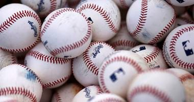Basket of Rawlings baseballs sits on a practice field