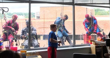 Window washers dressed as superheroes surprise Blank Children's Hospital kids.