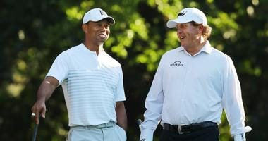 Tiger Woods and Phil Mickelson share a laugh on the 11th tee while playing a practice round for the 2018 Masters