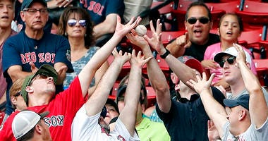 Boston Red Sox fans reach for a foul ball in the seats