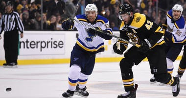 Boston Bruins right wing David Backes (42) skates after a loose puck ahead of St. Louis Blues left wing Jaden Schwartz