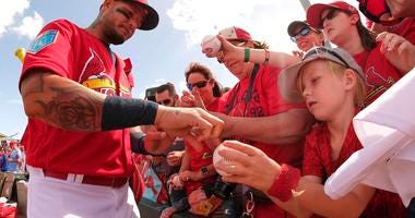 St. Louis Cardinals catcher Yadier Molina (4) signs autographs for fans before the game against the Houston Astros at Roger Dean Stadium.