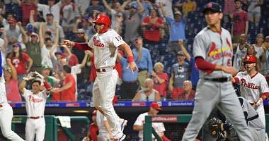 Philadelphia Phillies left fielder Rhys Hoskins (17) begins celebrating after a walk off win as St. Louis Cardinals relief pitcher Matt Bowman (67) looks on
