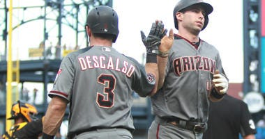 Arizona Diamondbacks second baseman Daniel Descalso (3) greets first baseman Paul Goldschmidt