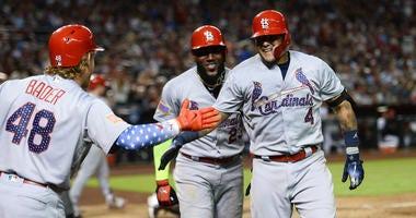 St. Louis Cardinals catcher Yadier Molina (4) celebrates with left fielder Marcell Ozuna (23) and center fielder Harrison Bader