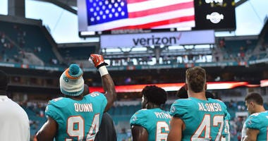 Miami Dolphins defensive end Robert Quinn (94) raises his fist during the national anthem