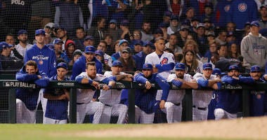Chicago Cubs players look on from the dugout in the bottom of the 13th inning