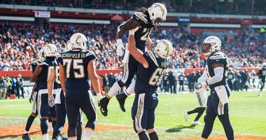 Oct 14, 2018; Cleveland, OH, USA; Los Angeles Chargers offensive guard Dan Feeney (66) holds up Los Angeles Chargers running back Melvin Gordon (28) after Gordon scored a touchdown during the second half against the Cleveland Browns at FirstEnergy Stadium