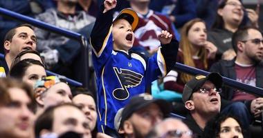 A St. Louis Blues fan dances in the stands