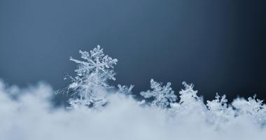 Snowflake. Macro photo of real snow crystal. Beautiful winter background seasonal nature and the weather in winter