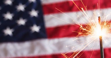 A fourth of july sparkler on a usa flag background.