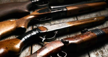 collection of hunting rifles. Rifles, shotguns on wooden table background, Hunting guns close-up
