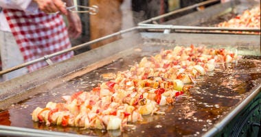 Appetizing meat and vegetables on wooden sticks frying in boiling oil at fair