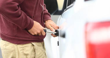 Stock image of someone breaking into a car.