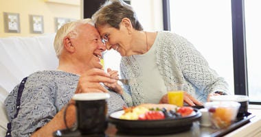 Senior Couple In Hospital Room As Male Patient Has Lunch Looking Into Each Others Eyes Smiling