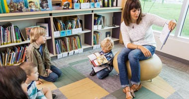 Young teacher reading book to children in library of elementary school