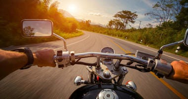 Driver riding motorcycle on the empty asphalt road