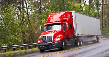 Big red semi truck shiny and wet from the rain with the reflection of light with a long distance measuring trailer with dust rain under the wheels and reflection of headlights on a wet road passing by green trees.