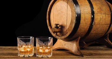 Whiskey and oak barrel on a black background