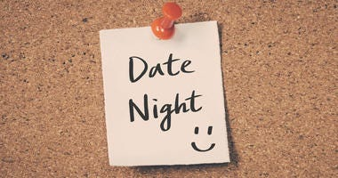 Date night reminder message on a cork board