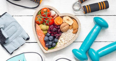 Food in heart and dumbbells fitness abstract healthy lifestyle concept on white boards