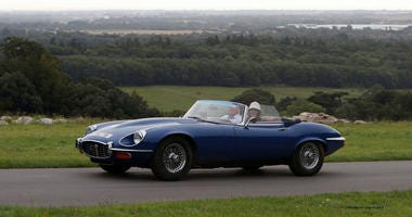Jaguar E-type cars set off from Goodwood House in West Sussex on the E-type Round Britain Coastal Drive