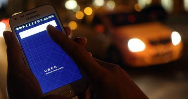 Person holding phone with Uber app open in front of traffic