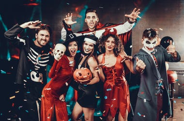 Portrait of Young Smiling People in Scary Costumes. Group of Young Happy Friends Wearing Halloween Costumes having Fun Together and posing for Group photo in Nightclub. Halloween Celebration