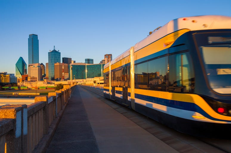 Moving streetcar on the Houston Street Viaduct with the city of Dallas in background
