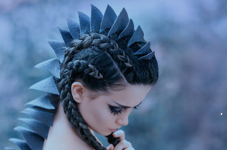 Dragon girl Black, sharp thorns cover the back and head of a young woman. Creative fabulous image of an alien humanoid creature. Unusual hairstyle with braids. Gothic dark makeup. Art retouching.