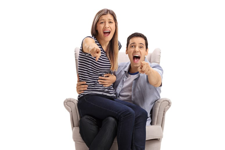 Happy young couple in an armchair pointing at the camera and laughing isolated on white background