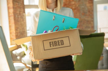 Young businesswoman fired, looks upset. Has to pack her office belongings and to leave work place for new worker. Problems in occupation, stress, unemployment, new way of life or end of career.