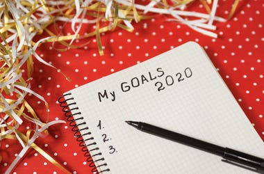 Phrase My Goals 2020 in a notebook, black pen. Red background and tinsel. New Years concept