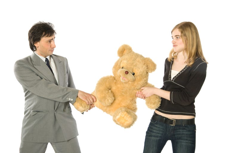 Young man and woman fighting over a teddy-bear
