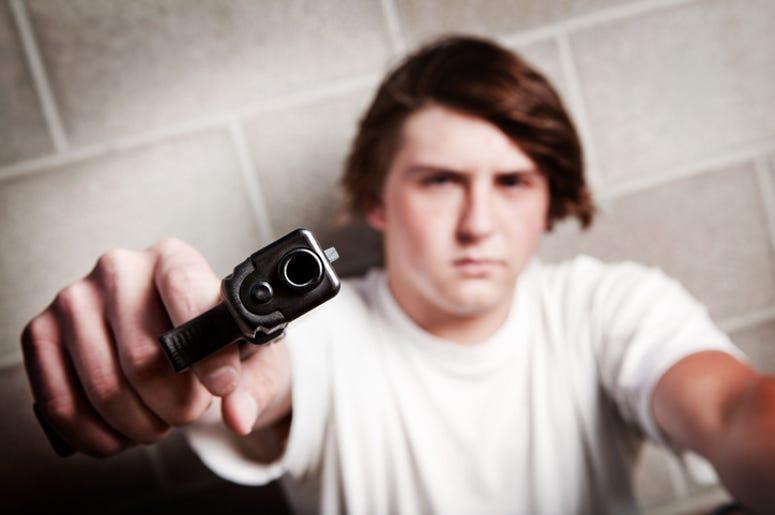 teenager male angry - pointing gun at camera