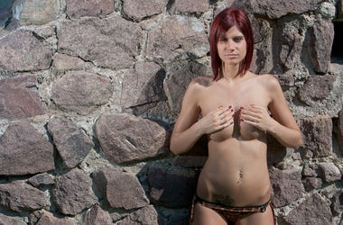 beautiful girl posing as a model in topless in the ruins of a castle