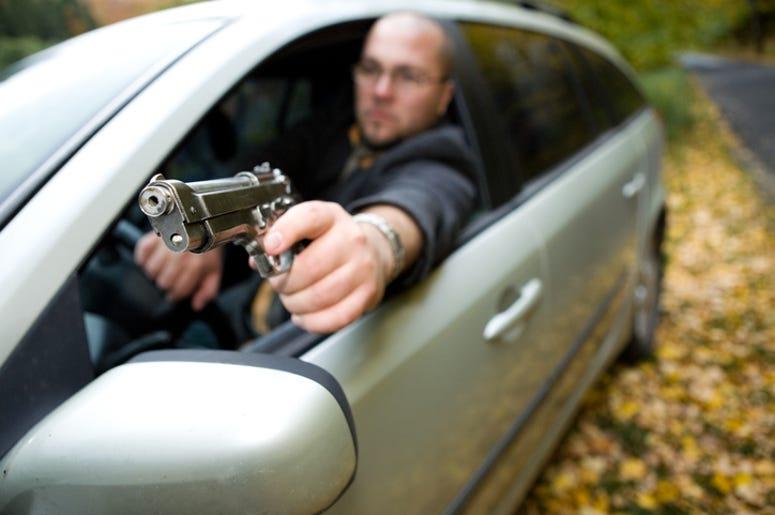 angry man with gun driving car
