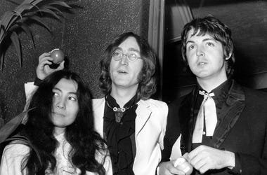 Beatle John Lennon (1940 - 1980) and his Japanese girlfriend Yoko Ono with Beatle Paul McCartney, right, at the premiere of the new Beatles film 'Yellow Submarine' at the London Pavilion. John and Paul hold apples, the symbol of their newly formed company