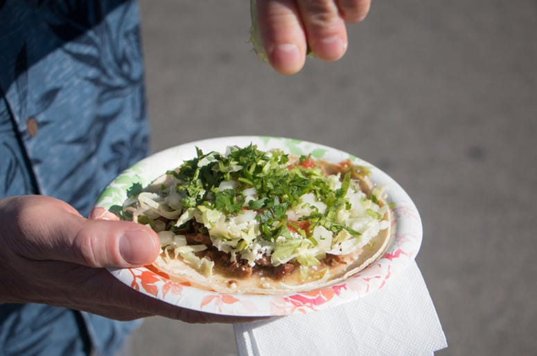 A lime is being squeezed onto a carne asada taco on a paper plate.