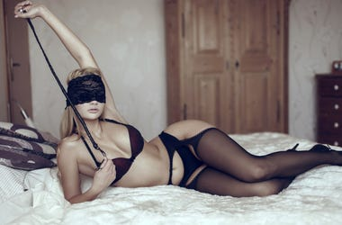 Sexy woman in lace eye cover with whip on bed, bdsm